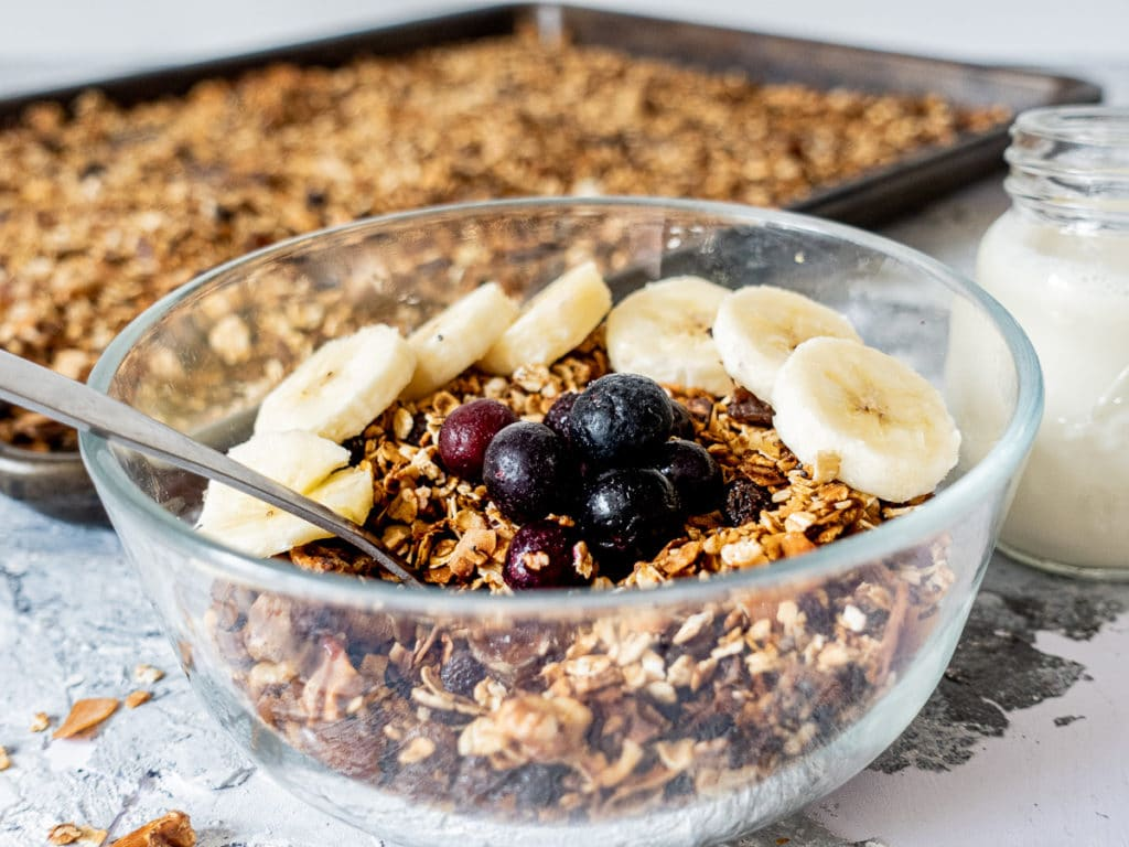 close up of bowl of granola with pan of baked granola in the background