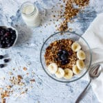a bowl of lemon poppysee granola with a glass of milk