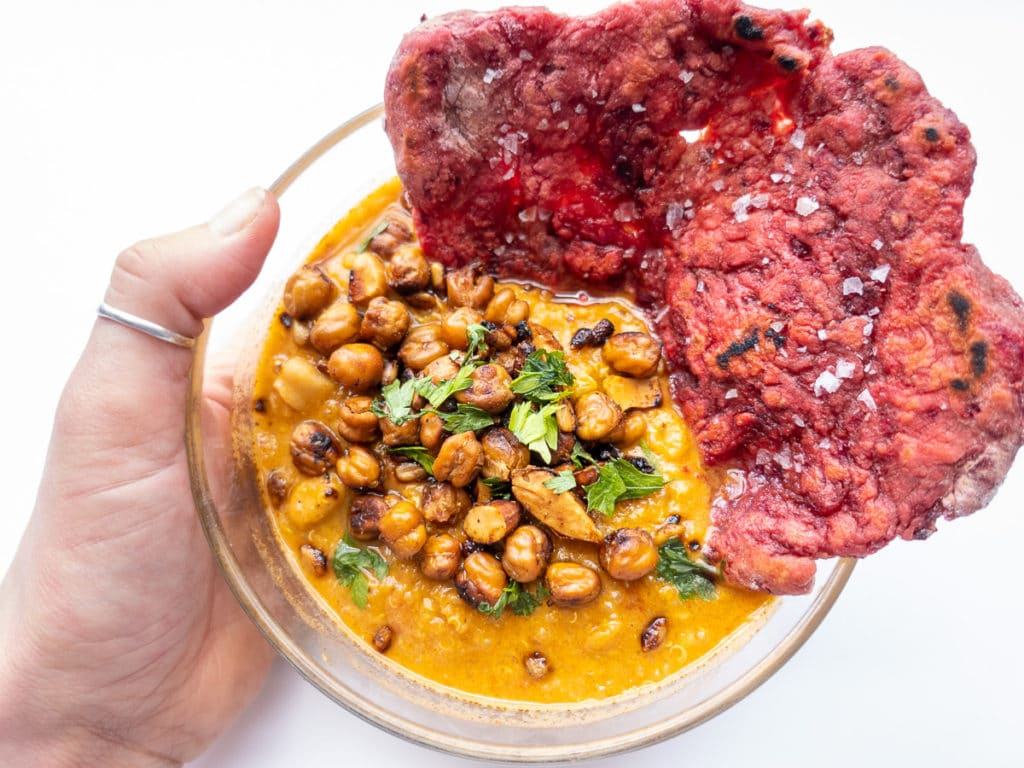 Bowl of Vegan African peanut soup with beet flat bread