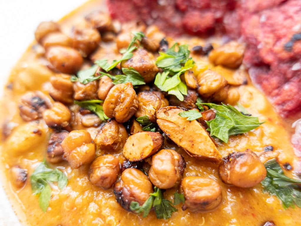 Close up of vegan African peanut soup with crispy chickpeas and roasted almonds.