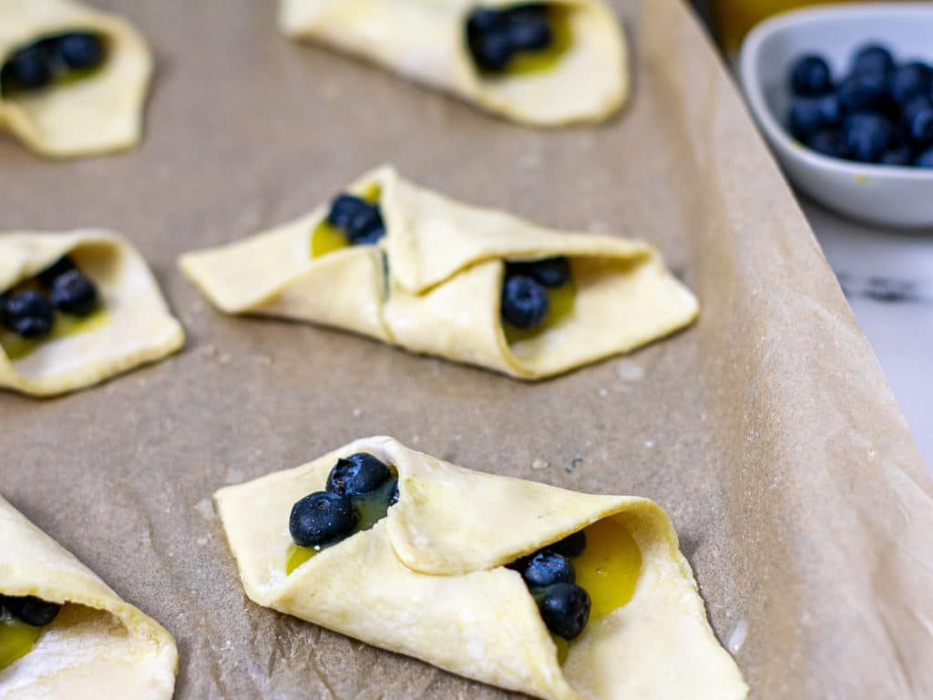 uncooked pastry dough stuffed with lemon curd and blueberries.