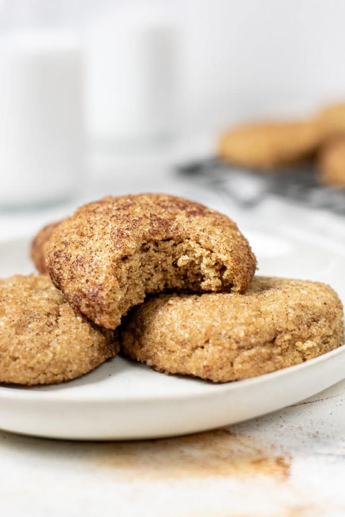 a heaping plate of vegan snickerdoodles made from almond flour. One cookie has a bite out of it!