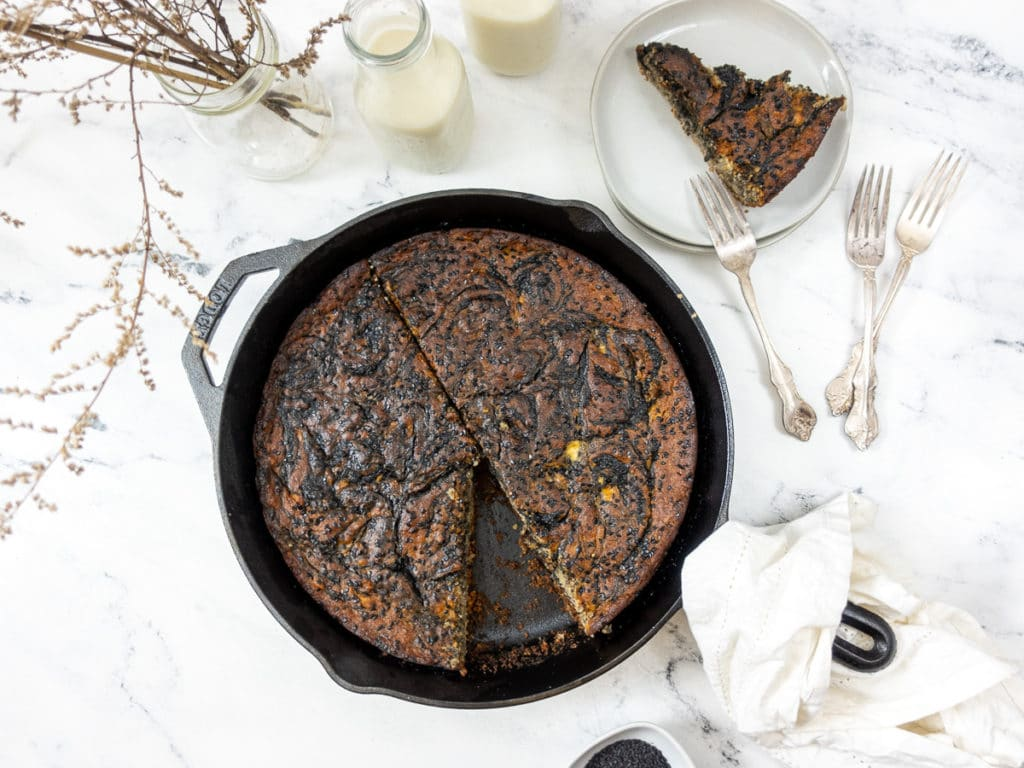 Tahini Banana Bread baked in a cast iron with a slice out of it.