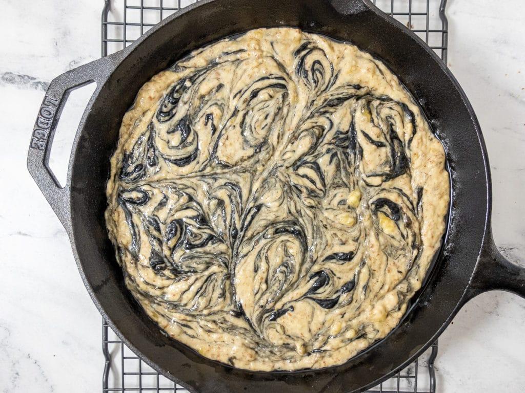 Swirls of black tahini in banana bread unbaked