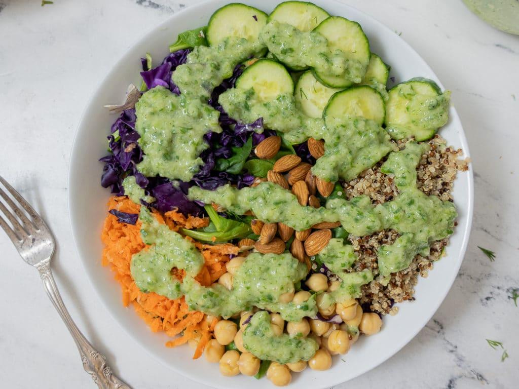 Fresh bowl of mixed veggies and quinoa drizzeled with vegan yogurt cilantro dressing.