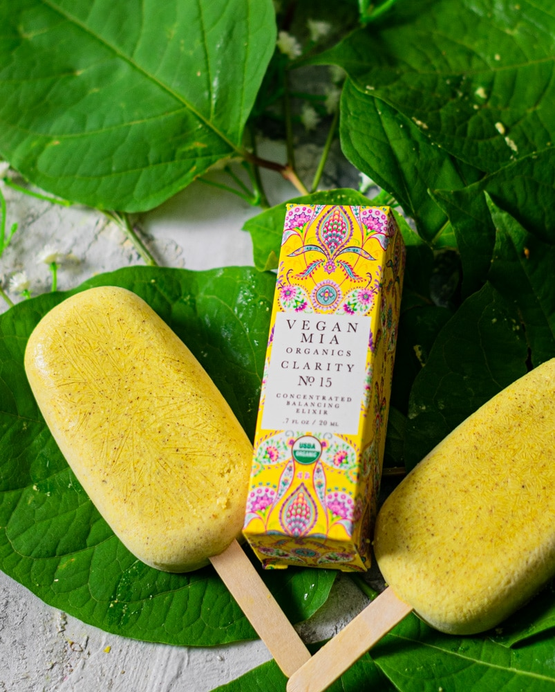 Two golden milk popsicles with a box of vegan mia organic skin care