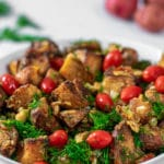 Close up of roasted potatoes and fresh herbs