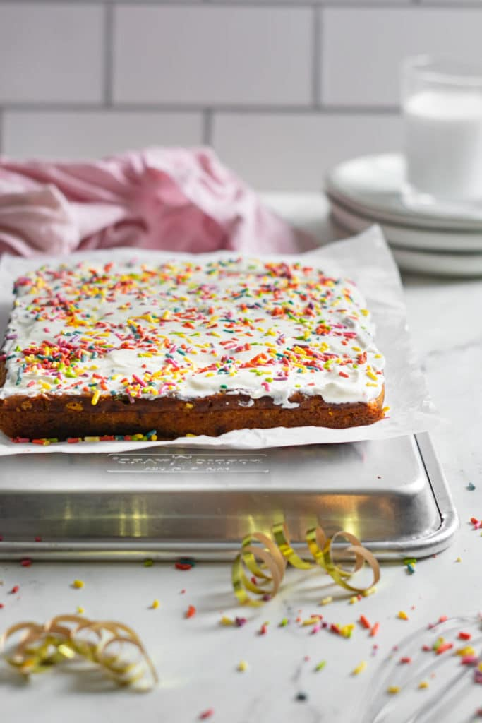 The whole cake before slicing with sprinkles on top.