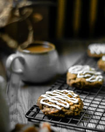 oatmeal cookies cooling on a rack with a cup of coffee