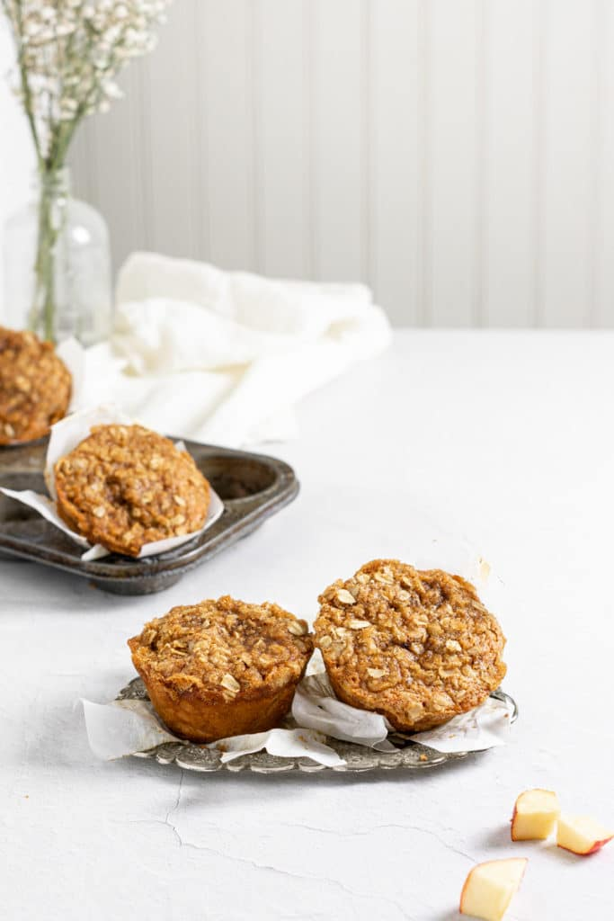 Apple cinnamon muffins on an antique plate with apples around