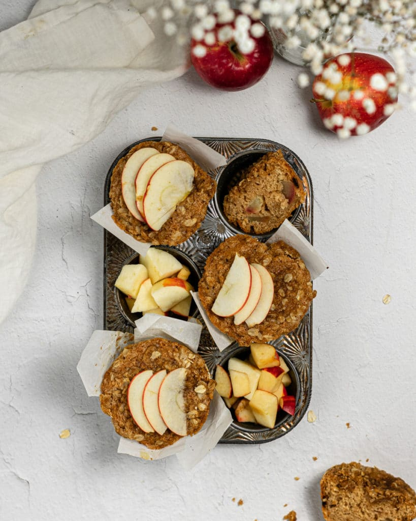 over head shot of muffins in a tin with slices of apples on top