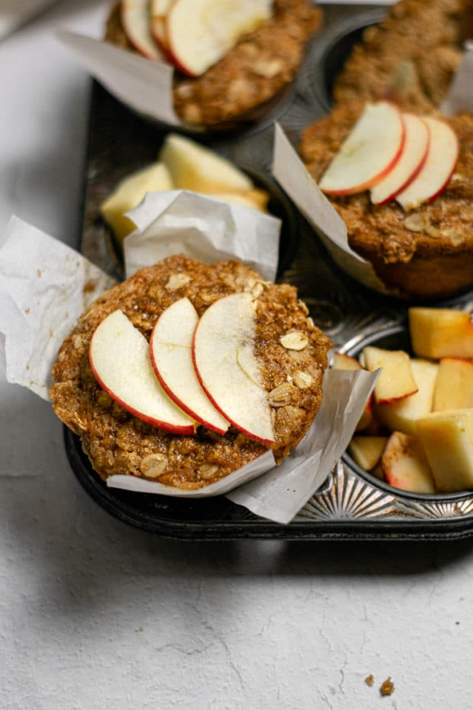 close up shot of apple muffins with sliced apples on top