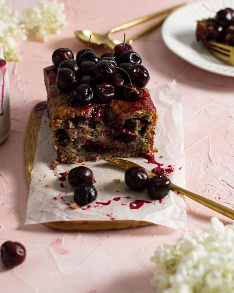A cut cherry loaf showing the moist inside full of juicy cherries.