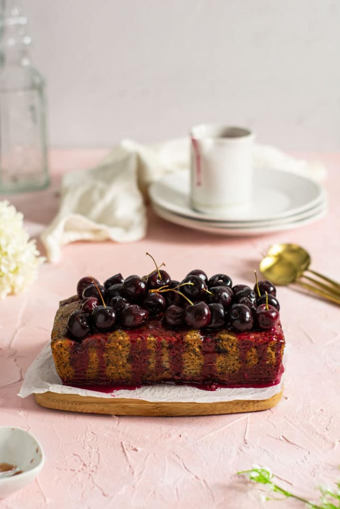 Baked loaf cake with vanilla drizzle and fresh cherries on top