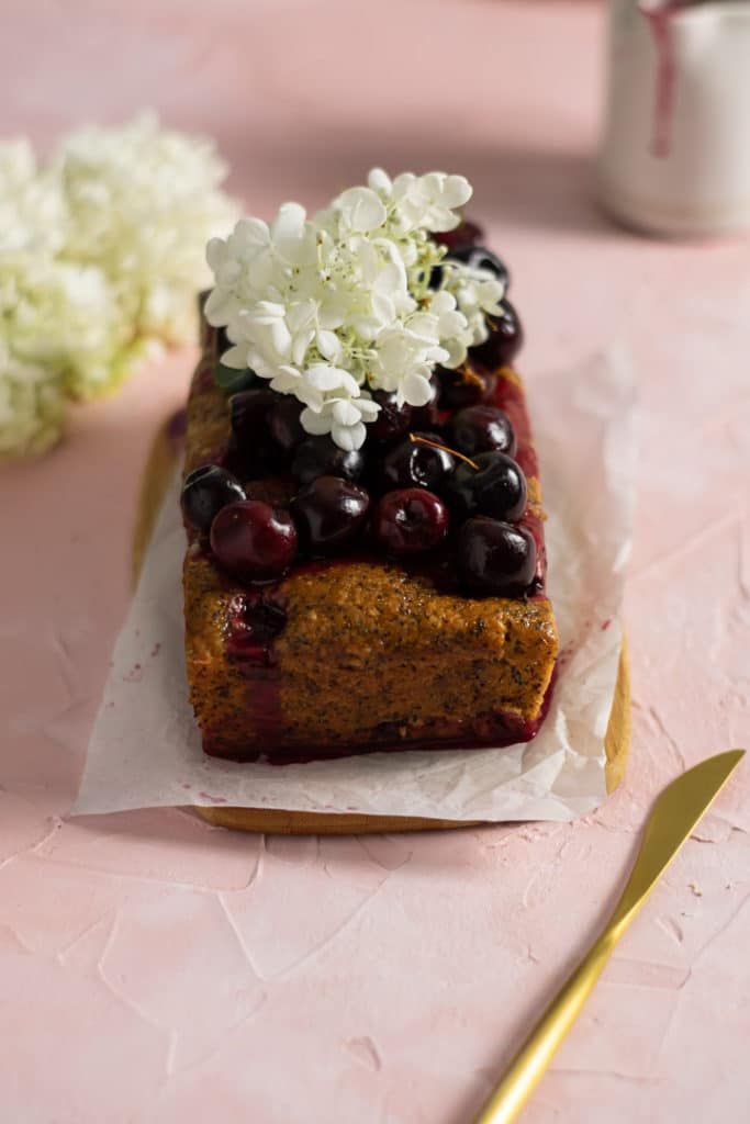 Cherry poppy seed loaf cake with cherries on top and fresh flowers.