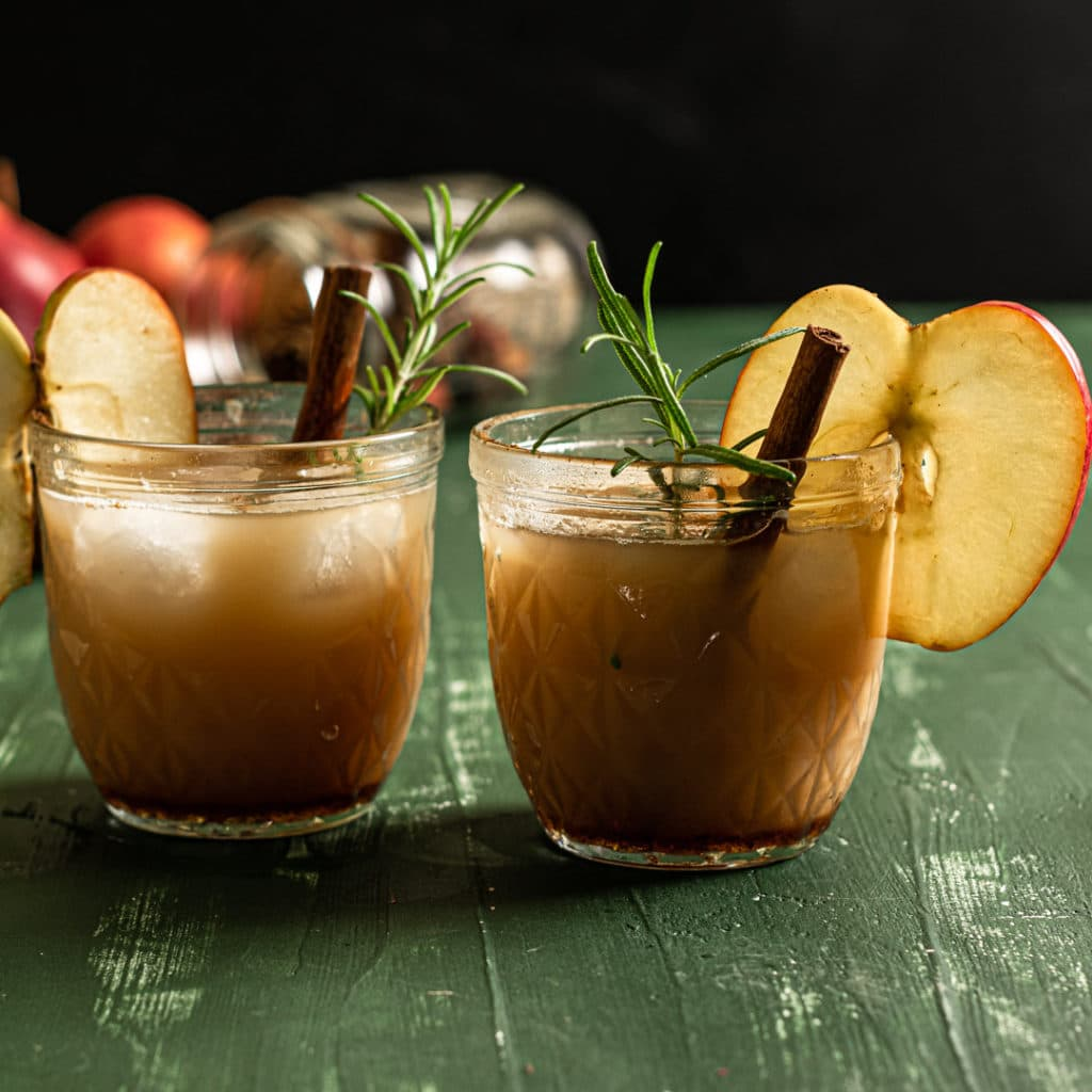two drinks with fresh rosemary and an apple slice.