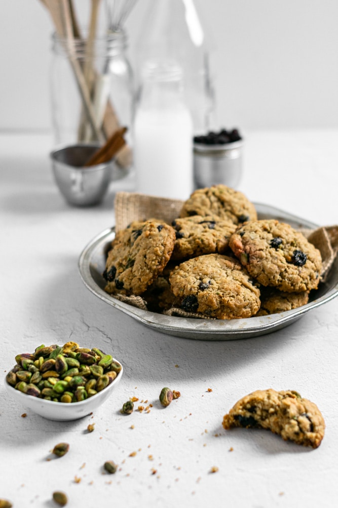 cookies in a pie dish with a bowl of pistachios near by