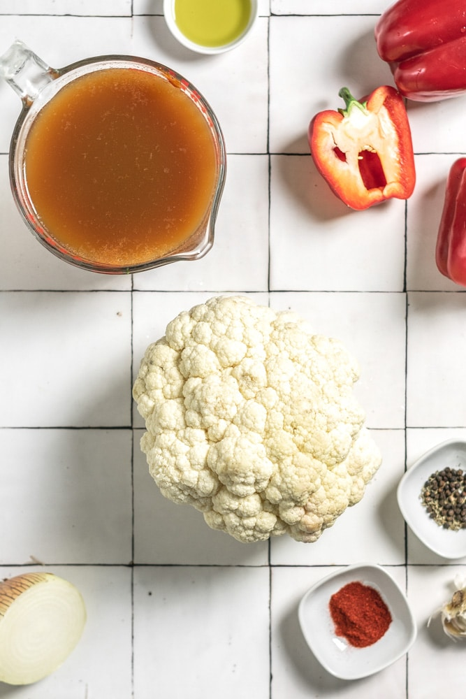 the ingredients to make soup, including red pepper, olive oil, cauliflower, vegetable broth, smoked paprika, thyme, garlic, and onion.