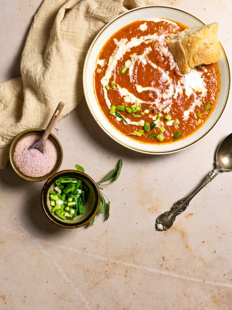 Roasted red pepper and cauliflower soup drizzled with coconut cream and served with fresh baguette.