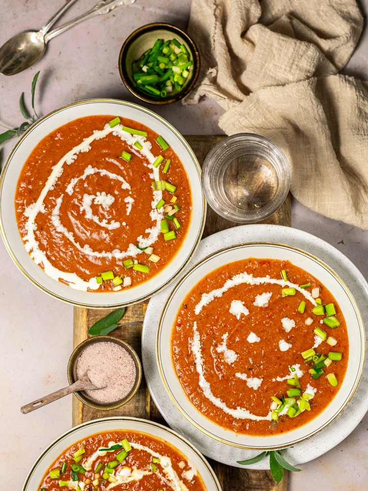 three bowls of soup drizzled with coconut cream and green onions on a table