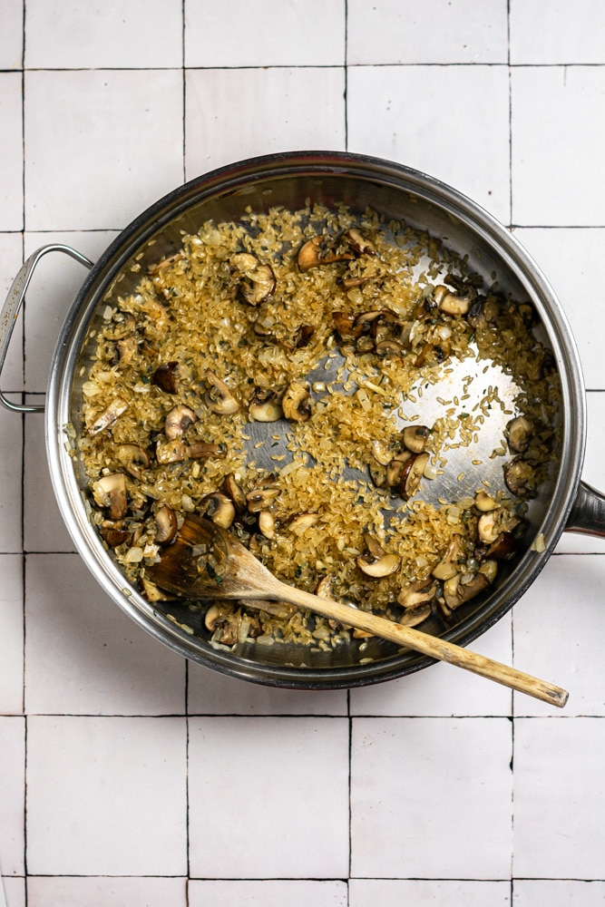 toasting the risotto rice with the mushrooms and onions