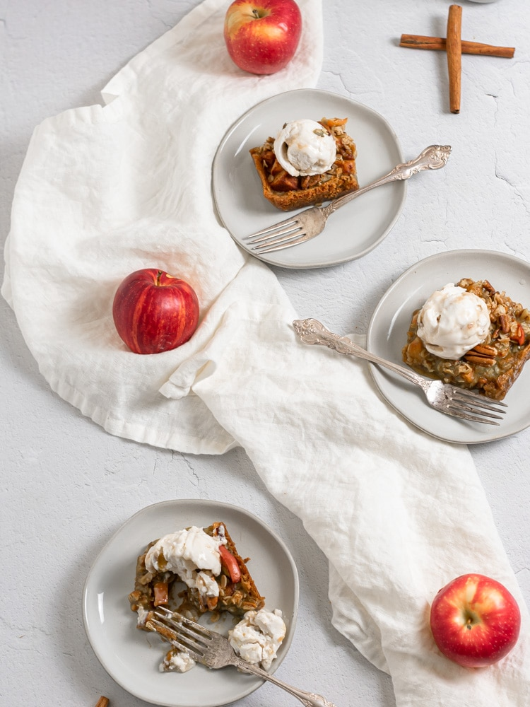 Three plates of apple pie bars with scoops of vanilla ice cream on top.