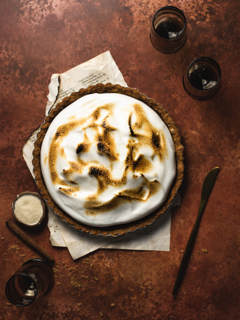 Table with toasted meringue topped mexican chocolate tart and glasses of wine.