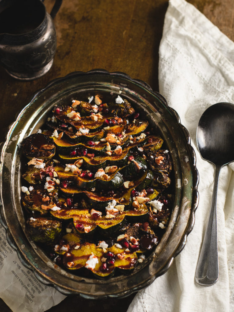 Side dish of roasted brussel sprouts and delicata squash set on the table.