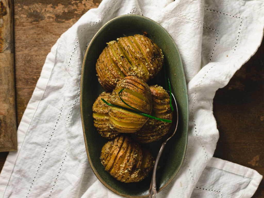 A dish full of hasselback potoatoes on the table.
