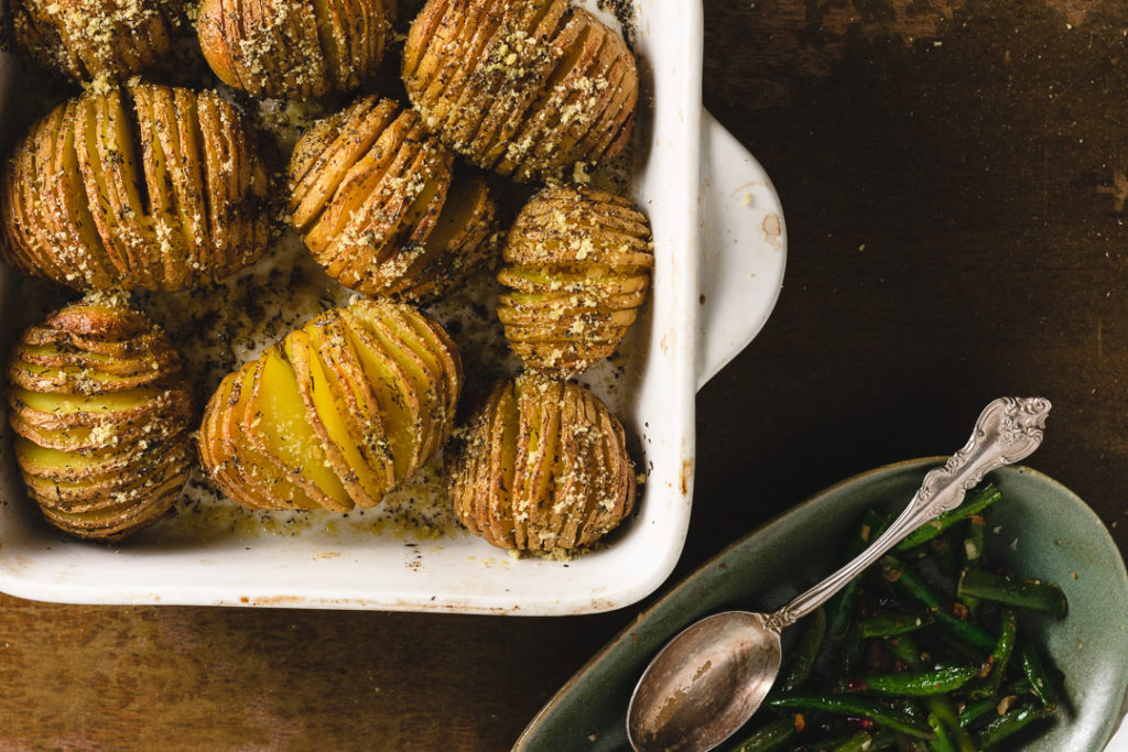 A table top with hasselback potatoes and greenbeans.