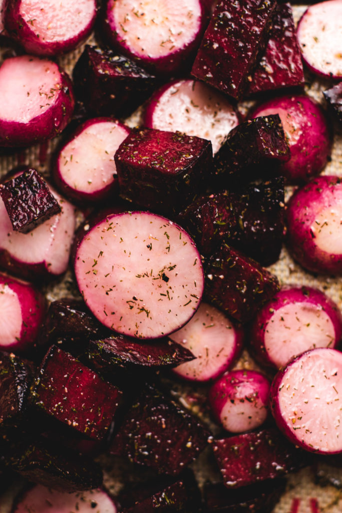 Radishes and beets coated in olive oil on a pan about to be baked.
