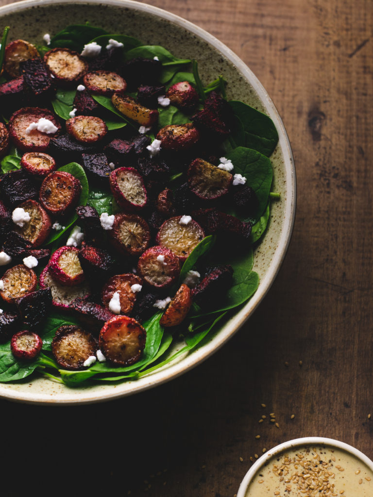 Table with big bowl of spinach salad and roasted root veggies