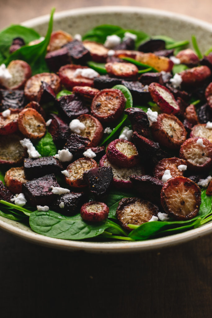 Big leafy spinach salad with roasted beets and radishes and topped with vegan feta.