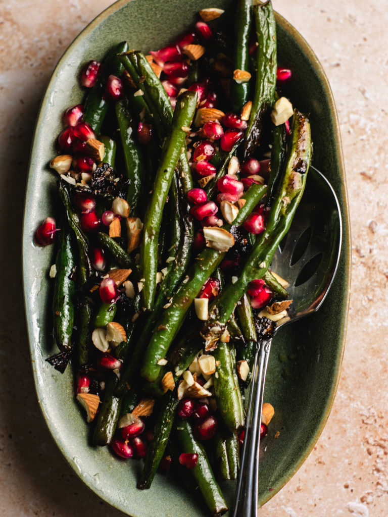 finished plate of garlic green beans with pomegrante seeds and almonds.