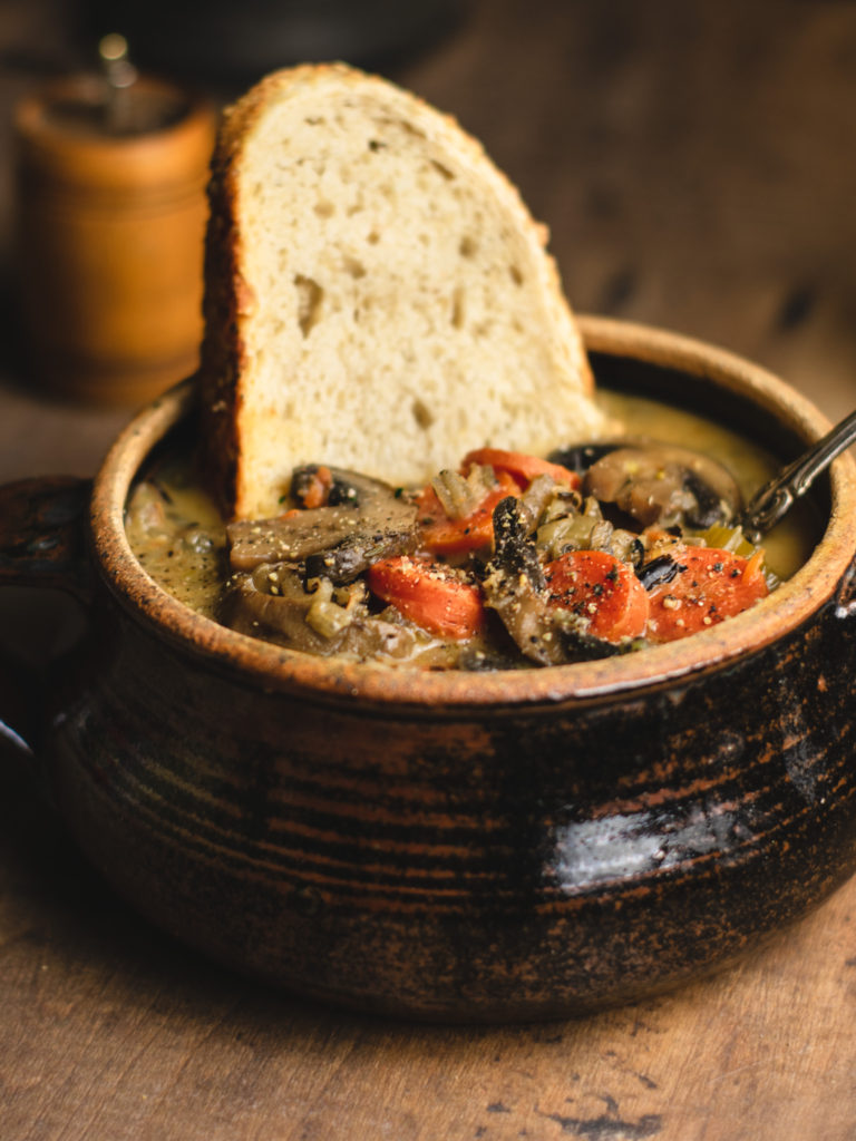 Close up shot of wild rice soup and a slice of bread