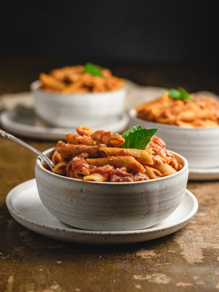 close up shot of a bowl of penne alla vodka pasta with fresh basil