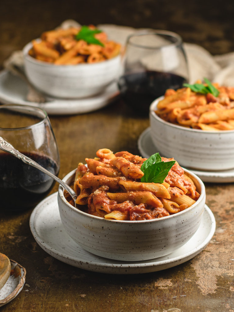 Bowls of penne pasta with red wine on the table.