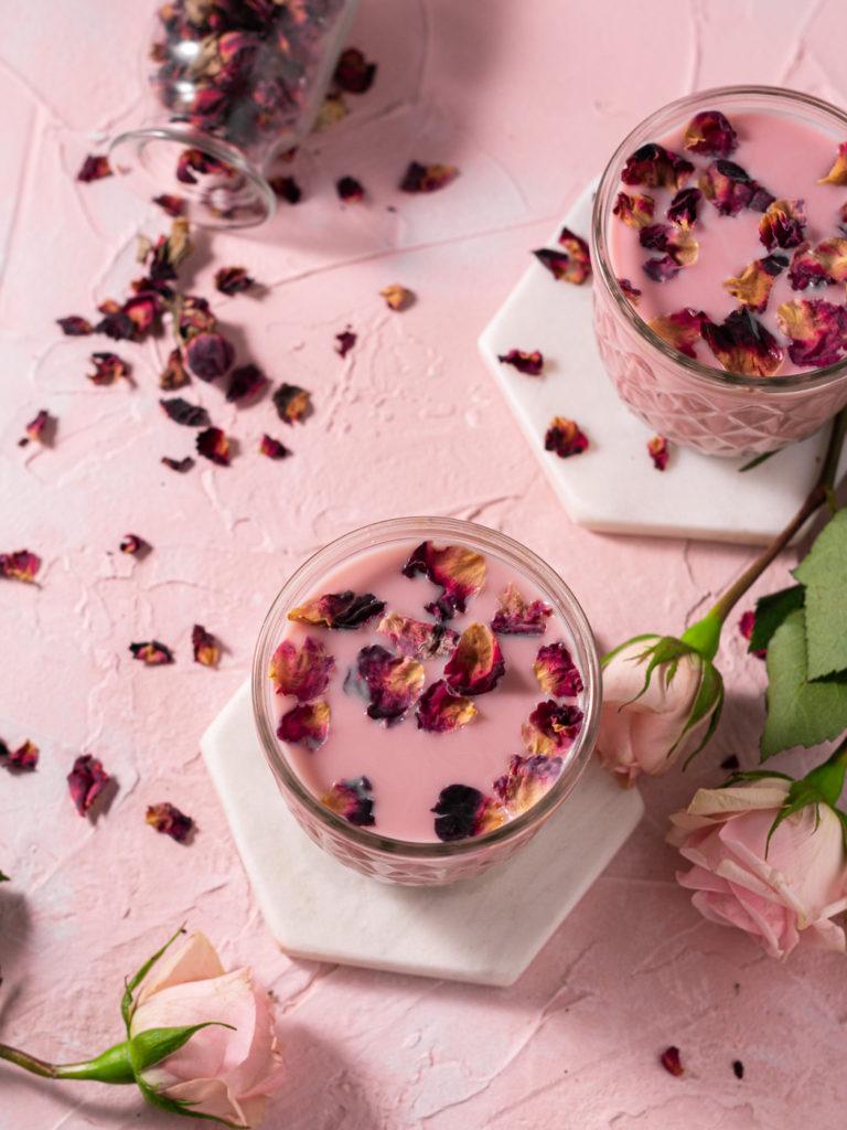 overhead flatlay shot of two glasses of moon milk, rose petals, ad fresh cut roses.