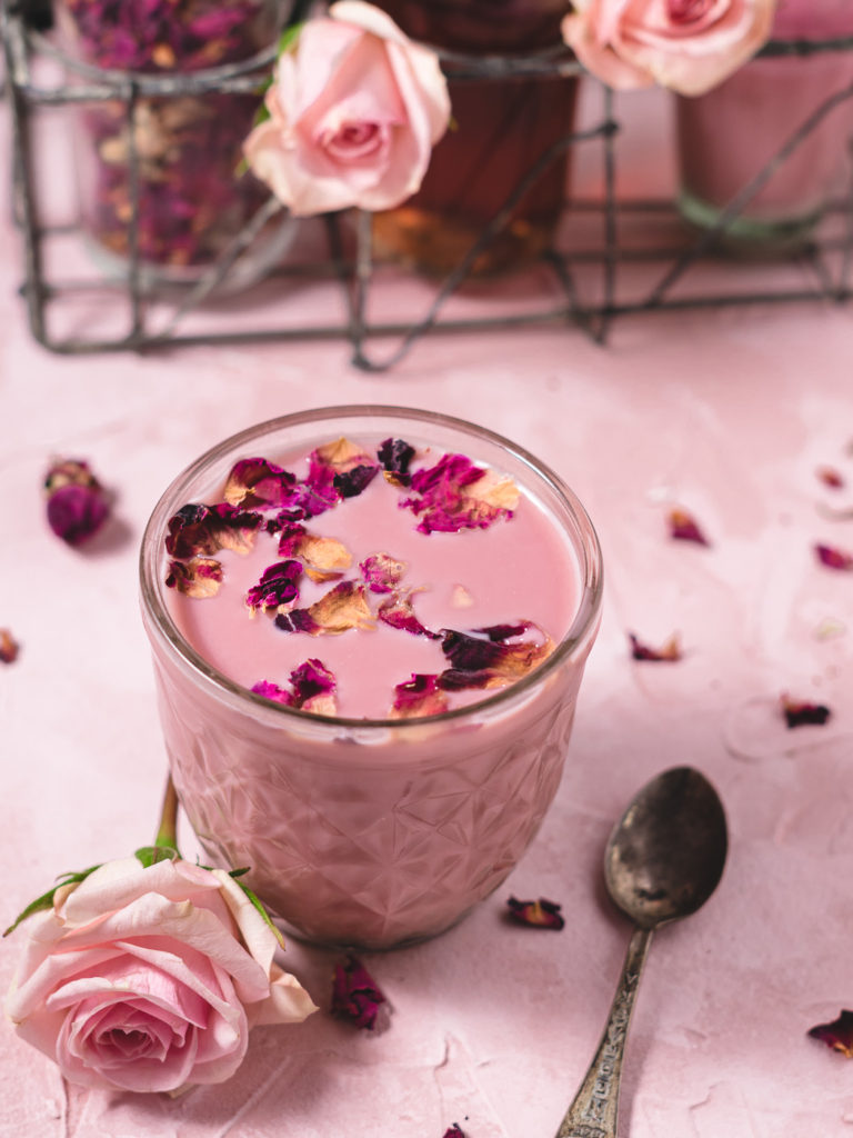 close up of a glass of moon milk with roses on top and the ingredients in the back ground.