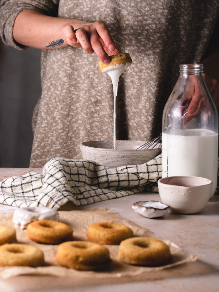 Dipping baked donuts in a bowl of vanilla bean glaze to coat the top.