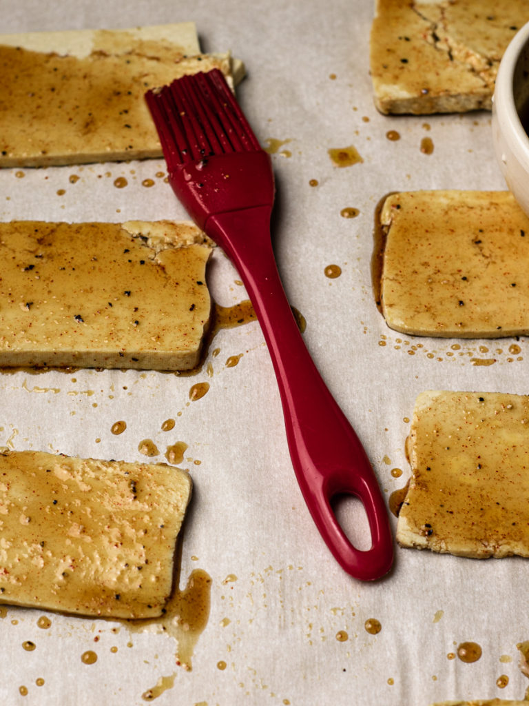 slices of fresh tofu brushed with a smokey sauce about to be baked in the oven.