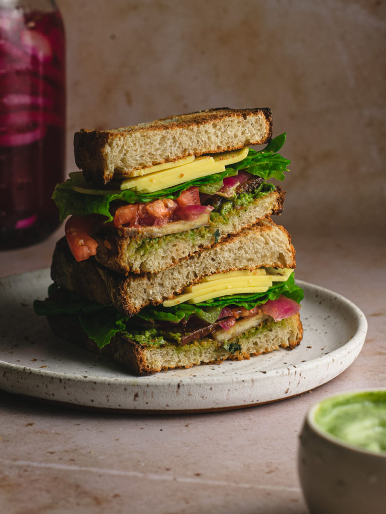 blt stacked high on a plate with pickled red onions.