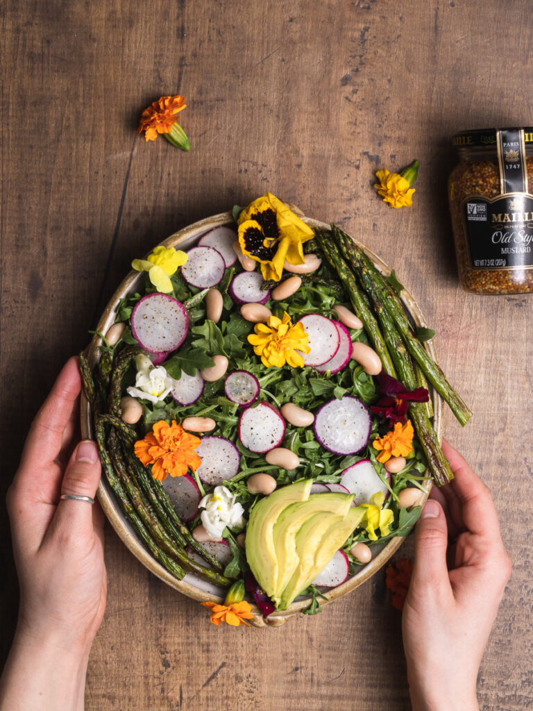 Serving a big bowl of salad with wild flowers and mustard dressing