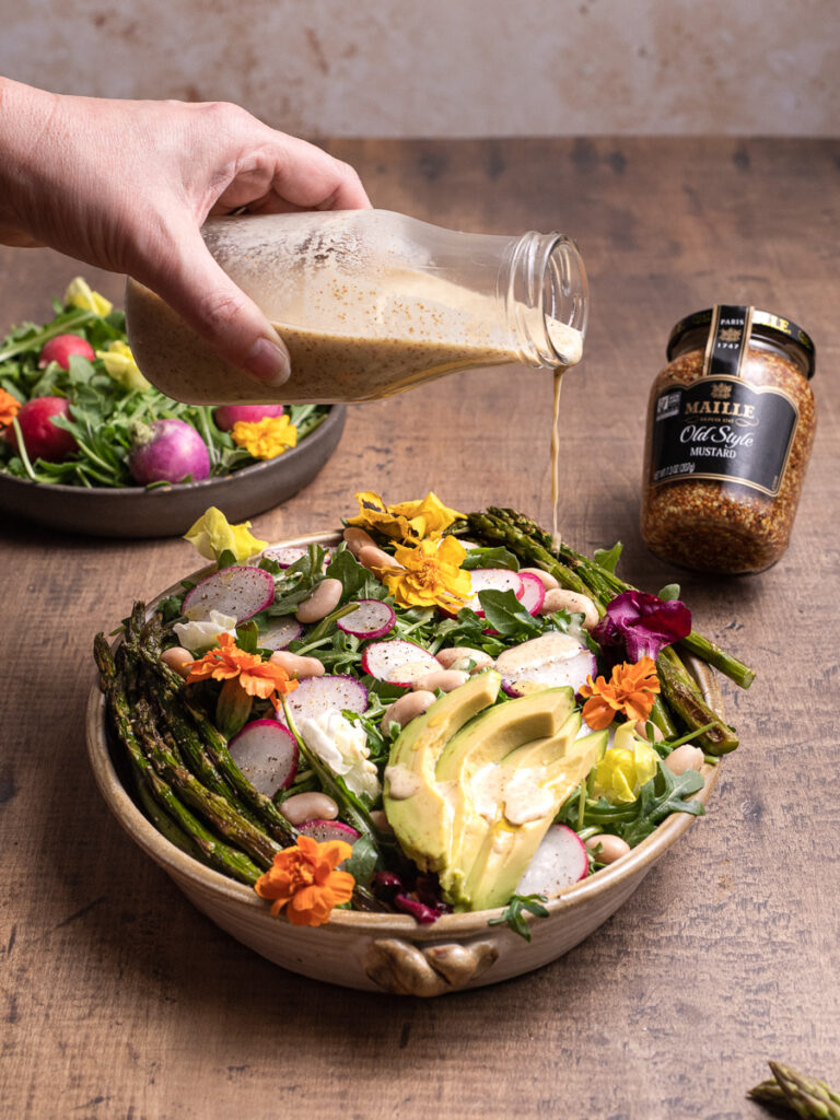 Drizzling creamy mustard dressing over a garden fresh salad. Featuring wild flowers, fresh avacado, and asaparagus.