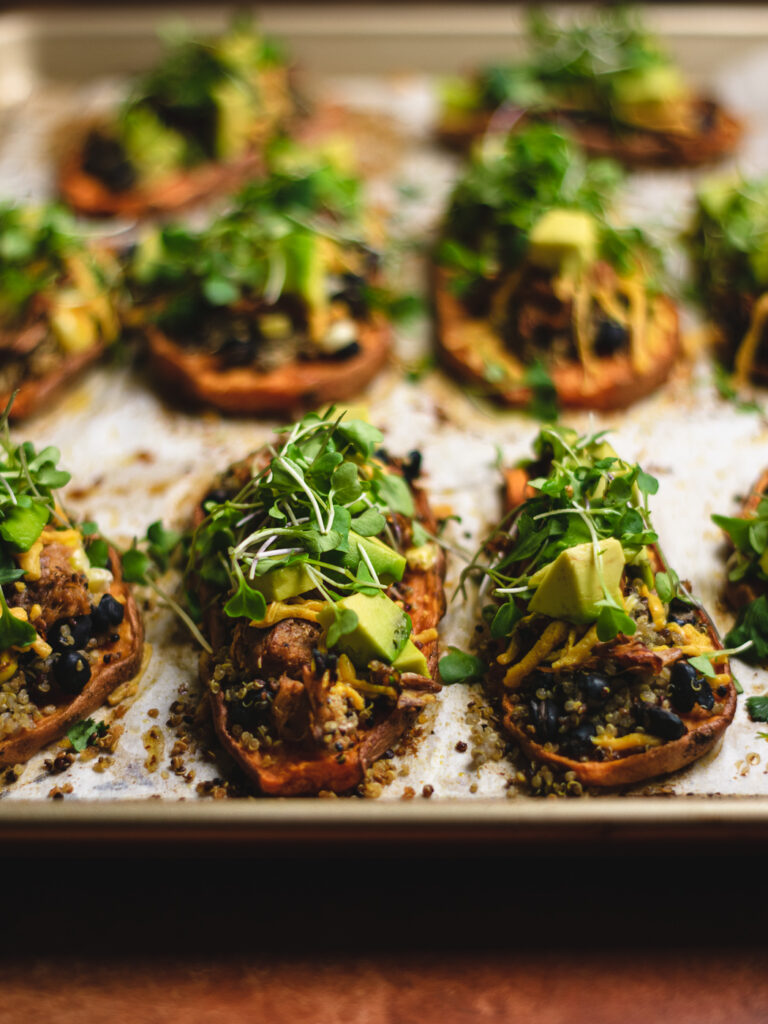 Pan of assembled sweet potato skins topped with avacado