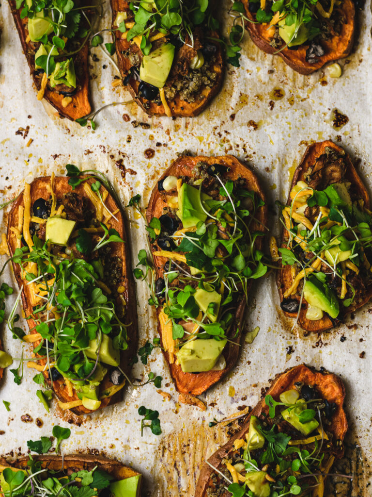 OVerhead shot of parchment paper with loaded sweet potato skins on it.
