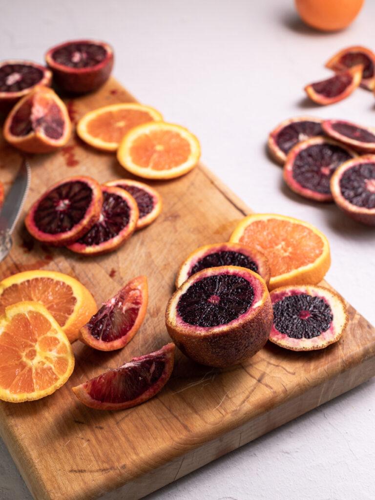 Sliced blood and cara cara oranges on a cutting board.