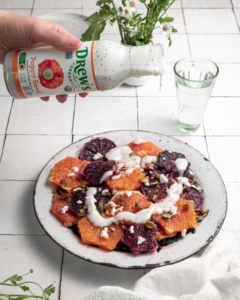 Drizzling poppy seed dressing over orange arugula salad.