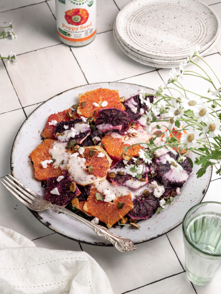 big plate of juicy cara cara and blood oranges with poppy seed dressing
