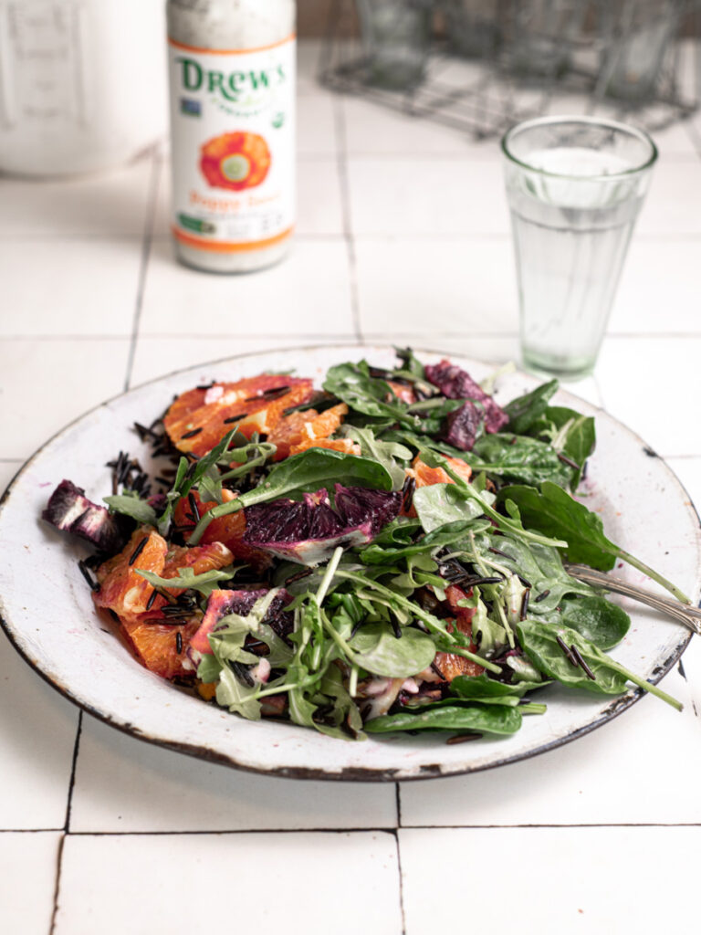 Mixed and tossed arugula salad with dairy free dressing and vegan feta cheese.
